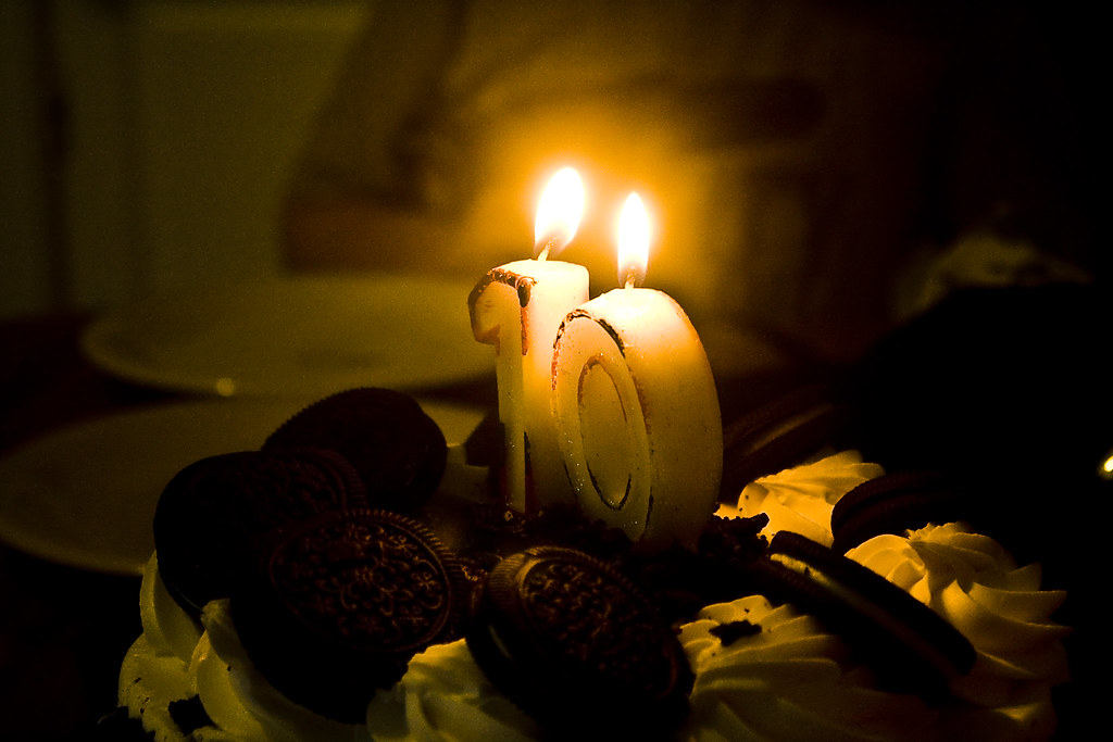 """A cake with lit candles in the shape of the number """"1"""" and """"0"""""""