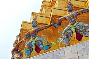 Colorful Thai caryatids holding up a golden roof