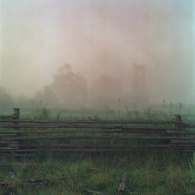 A wooden fence in a misty green field