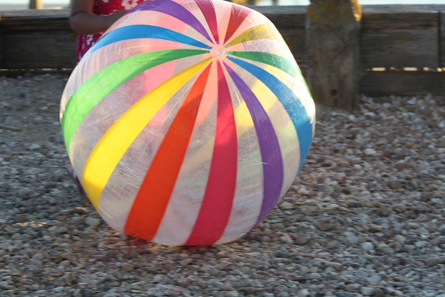 A rainbow colored beach ball sitting on the ground