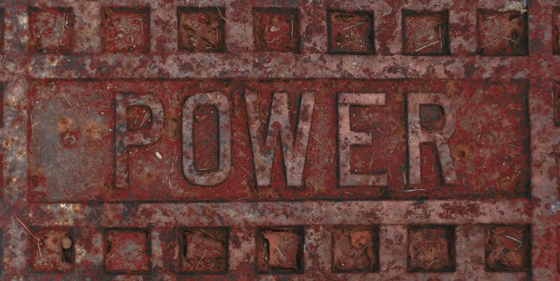 A rusty red utility cover with the word