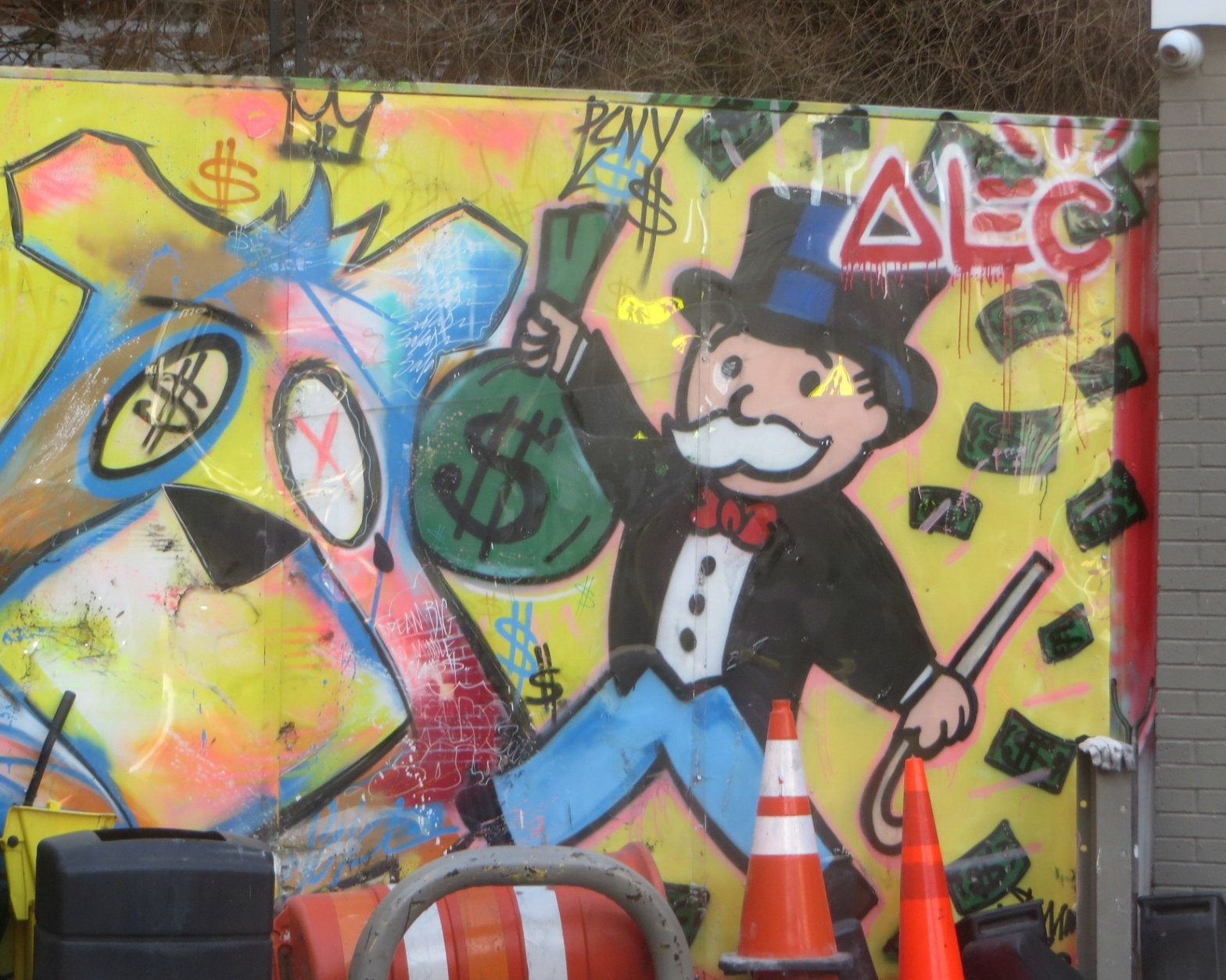 Graffiti of the Monopoly Man holding a bag of cash