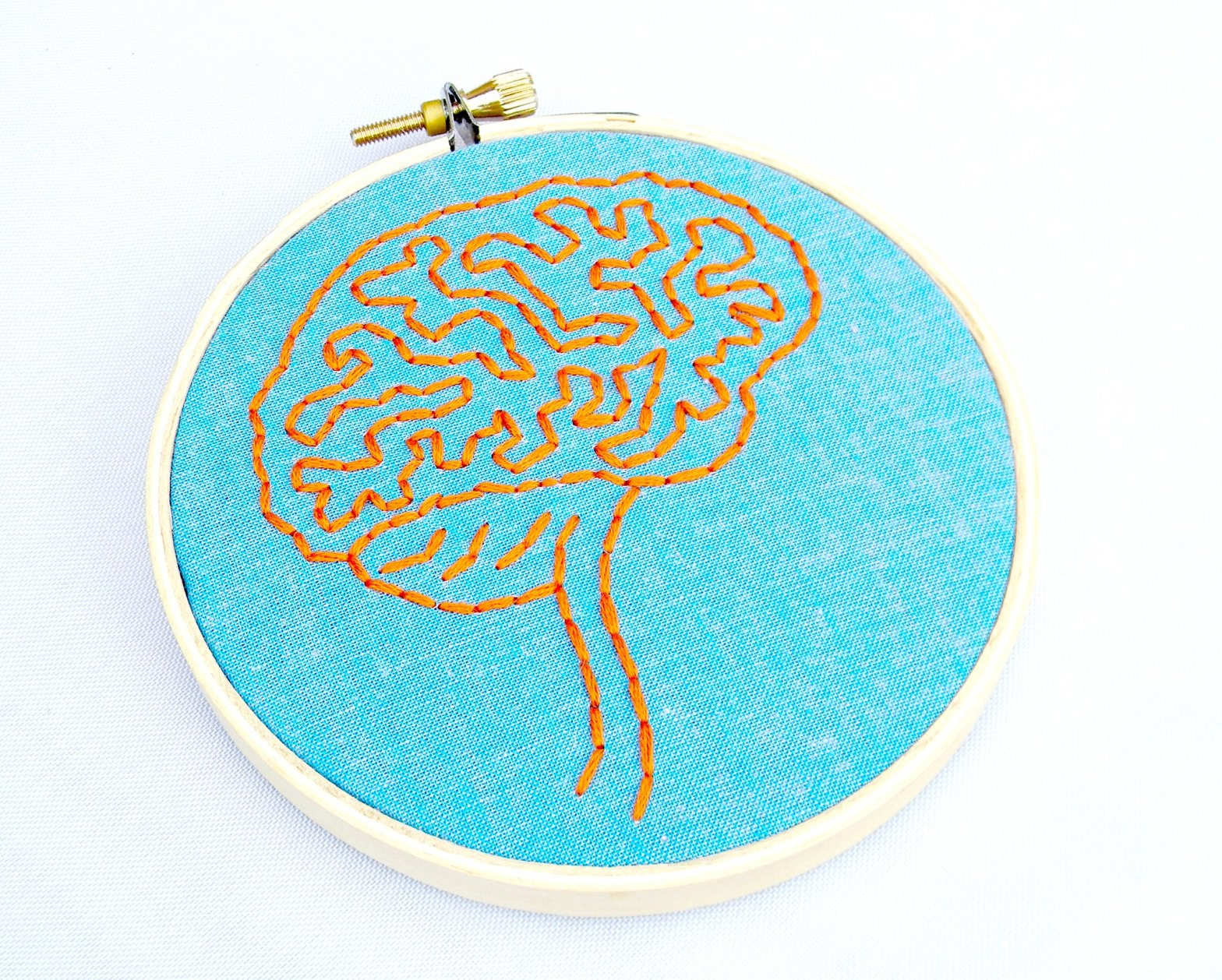 An embroidery hoop with a blue background and a brain outline embroidered in orange