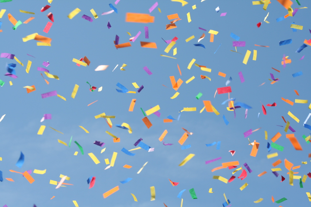 Multi-colored confetti with a blue sky in the background