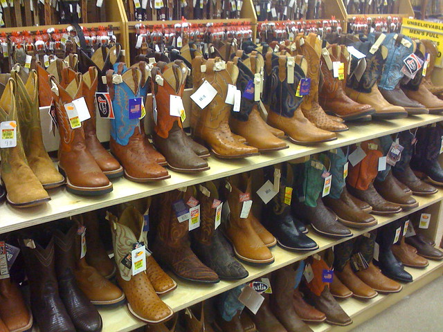 Shelves displaying dozens of different cowboy boots for sale