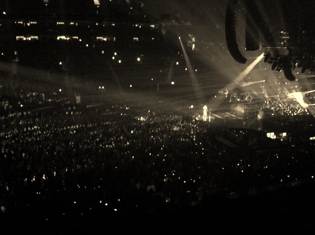 A huge arena of people with a performer highlighted by spotlights